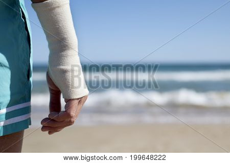 closeup of a young caucasian man in swimsuit on the beach with a bandage in his wrist, in front of the sea, with a negative space on the right
