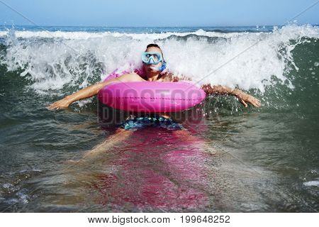 a young caucasian man wearing a diving mask, a snorkel and a pink swim ring into the seawater, next to the seashore