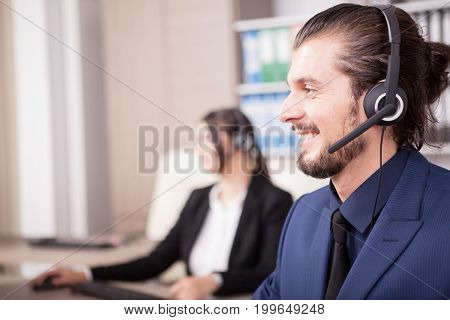 Portrait of man from customer support line in the office and his colleague blurred on the background. Help desk and support