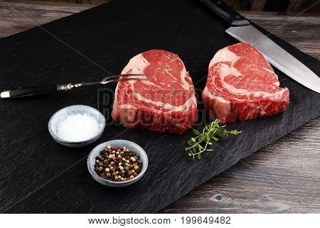 Raw Fresh Meat Ribeye Steak, Seasoning And Meat Fork On Dark Background