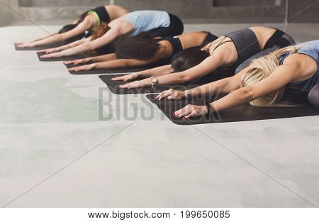Women in yoga class, half tortoise pose stretching. Healthy lifestyle in fitness club.