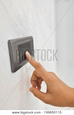Close up hand turning on or off on grey light switch with white marble background.