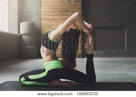 Young woman in yoga class making asana exercises. Girl do mermaid pose. Healthy lifestyle in fitness club.