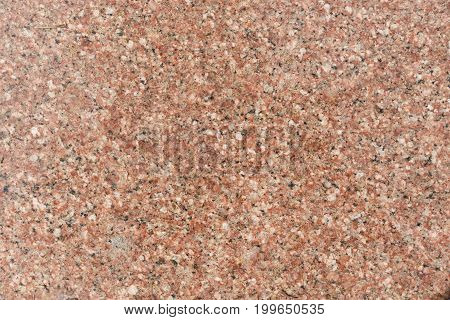 Red granite slab with black patches background. Kitchen wall or bathroom