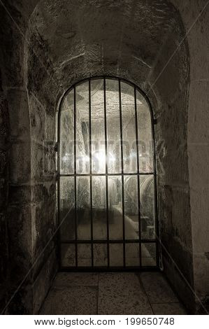 An old window with a lattice in a cellar or in a prison a window in an old wall