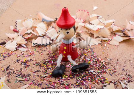 Pinocchio doll sitting amid colorful pencil shavings