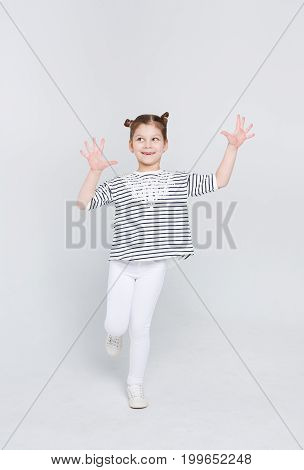 Emotional full length portrait of cunningly smiling girl showing her palms at studio on white background. Funny sly child displaying empty hands, posing on camera, copy space