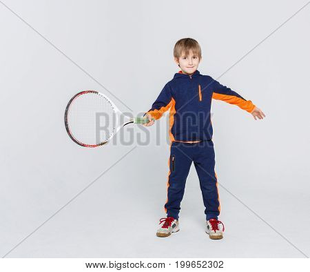 Portrait of happy little boy with tennis racket on white studio background. Young player in sportswear smiling and posing on camera. Active and healthy lifestyle concept. Vertical, copy space