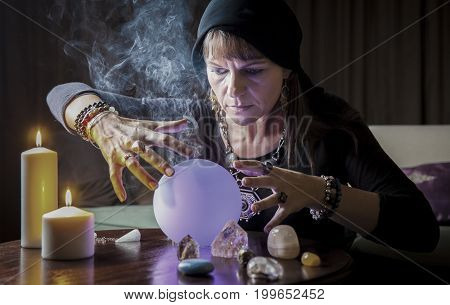 middle aged woman with reading fortune in candellight