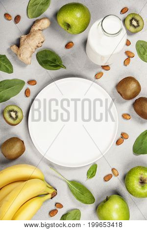 Variety of fresh fruits and nuts for healthy eating or making green smoothie over light grey background, top view. Healthy eating, vitamin, detox, diet food, clean eating concept