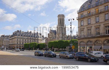 ParisFrance- April 30 2017: Back when the Louvre was still a royal palace (Palais du Louvre) Église Saint-Germain l'Auxerrois was its church.Pedestrians and vehicles move nearby