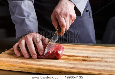 Man slicing filet mignon on wooden board at restaurant kitchen. Chef preparing fresh meat for cooking. Modern cuisine backgroung with copy space
