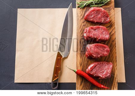 Raw filet mignon steaks. Fresh beef meat, rosemary and chilli on wooden board on craft paper at back background. Organic ingredients for restaurant meals and sharp chef knife , top view, copy space