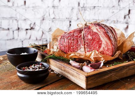 Raw black angus beef bound with rope in craft paper on cutting board. Aged prime marble meat, herbs and spices rustic wood against white brick wall background with copy space