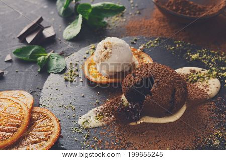 Exquisite french dessert. Chocolate fondant with creme anglaise and vanilla ice cream, sprinkled with cocoa powder, served on round slate decorated with orange citron and pistachio crumble, closeup
