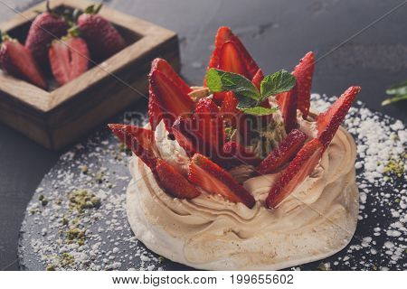 Fitness restaurant dessert at black background. Anna Pavlova meringue with low-fat whipped cream and fresh strawberry on slate sprinkled with powdered sugar and pistachio crumble, closeup, copy space
