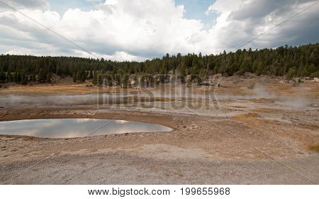 Firehole Lake and hot spring pool in the Lower Geyser Basin in Yellowstone National Park in Wyoming United States