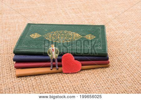Figurine Beside A Heart Standing On  Books