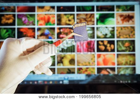 Digital memory card for photography and video. A storage medium on the background of a monitor with many photographs
