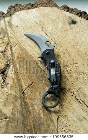 Tactical Knife In A Wooden Background. Knife With Clip And Ring.