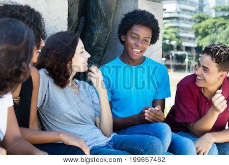 Group of talking african american and latin and caucasian people outdoor in the summer