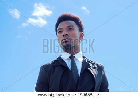 young african man suit and tie blue sky low angle view businessman successful future