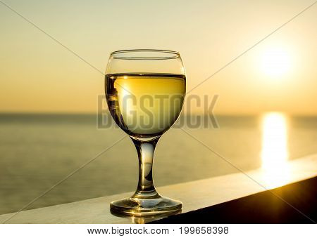 glass of white wine on a sunset background in the sea