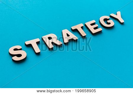 Word Strategy on blue background. Business plan, mission concept
