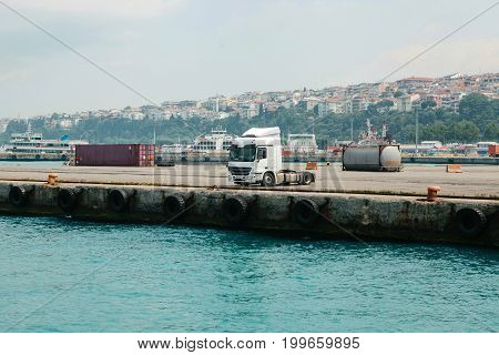 Panoramic view of cargo truck parked at the sea port, city view on the background.