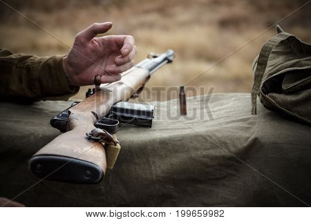 Old military rifle. Next to the rifle shell casing and soldier's hand