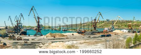 Landscape of tugboats and cranes in shipyard in coast. Panoramic image