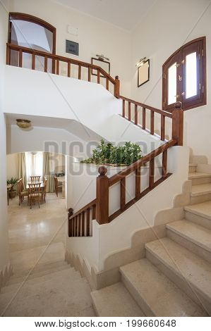 Marble Staircase In Luxury Villa Home With Wooden Bannister