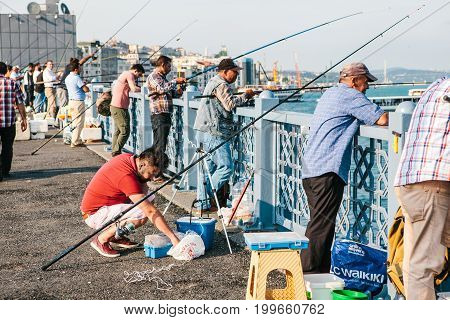 Istanbul, June 15, 2017: Many fishermen from the local population stand on the Galata bridge and fish.