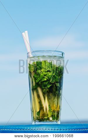 One misted glass of cocktail mojito over blue sky background