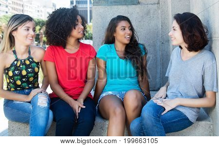 Talking and relaxing group of young woman outdoor in the summer in the city