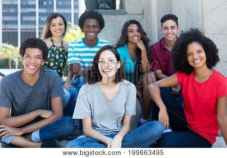 Large group of happy multiethnic young men and women outdoor in the summer in the city