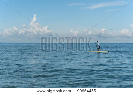 Clear-water, FL, USA - July 21, 2017. Young man sails on stand up paddle board on the Gulf of Mexico