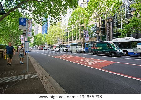 Sydney Australia - October 21 2015: People walking on a roadside near St. James Station bus stop and generic view of eastern suburb street in Sydney.
