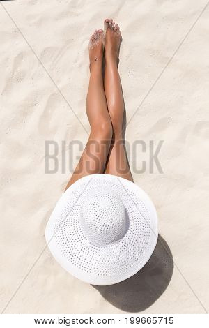 Summer Holiday Fashion Concept - Tanning Woman Wearing Sun Hat At The Beach On A White Sand Shot Fro