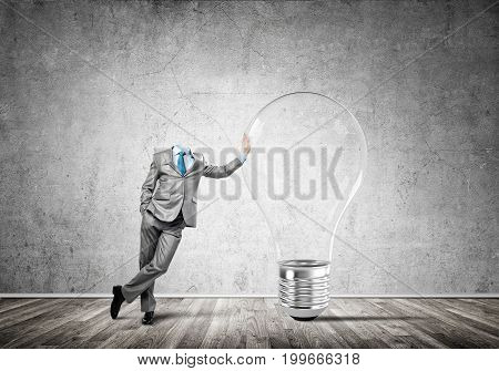 Headless businessman in empty room leaning on glass light bulb
