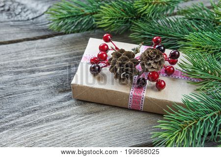 Christmas composition of pine cones spruce branches and gift box with fir cones and holly berries on the background of old unpainted wooden boards; with copy-space