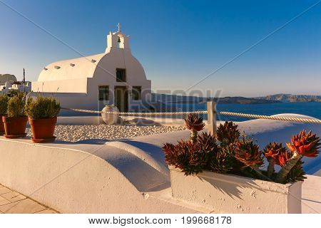 Picturesque view of Typical Greek white church in Oia or Ia over the sea, island Santorini, Greece