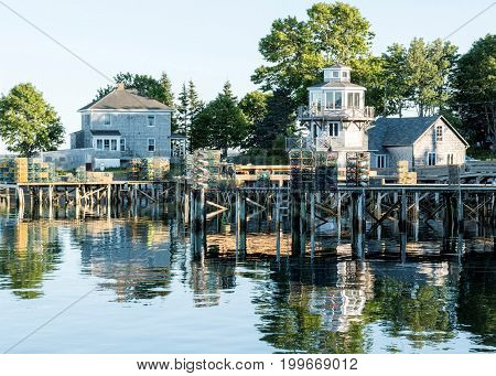 The coastline of bass harbor Maine with houses trees and their lobster traps stacked on docks all reflecting in the water