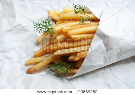 Potatoes French Fries In A White Paper Bag On A Sheet Of Light Paper.