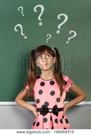 Child with question mark on school blackboard