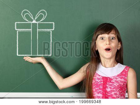 surprised girl hold drawn gift near school blackboard