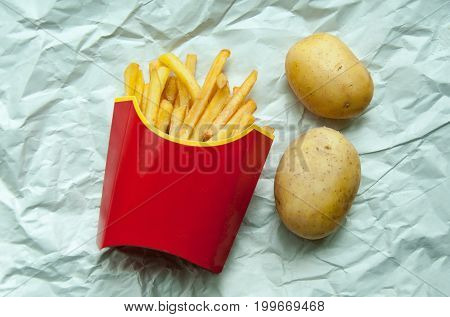 French Fries Potatoes In A Red Paper Bag And Two Whole Potatoes On A Light Background.