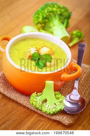 Tasty broccoli cream soup with crackers and parsley served on the burlap napkin, healthy eаting concept