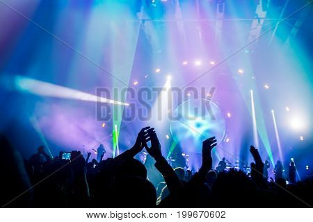 Many people enjoying concert, band performs on stage in the bright blue light, people enjoying music, dancing with raised up hands and clapping, active night life