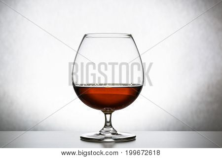 Glass with cognac on white background isolated. Front view. Close up shot. High resolution.